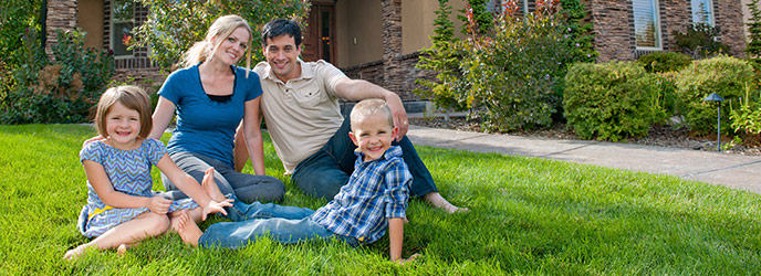 Family on Grass in Front of Home